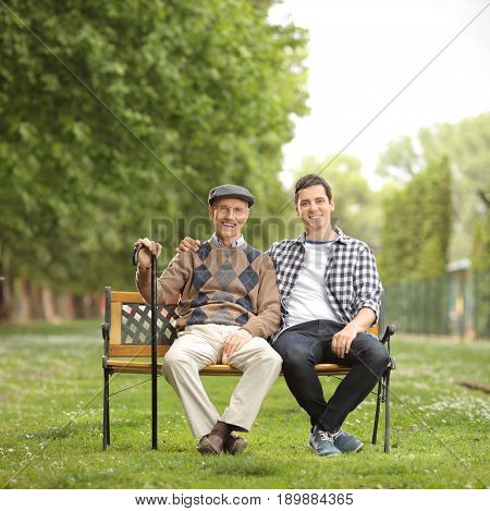 Grandfather with his grandson sitting on a bench in the park and looking at the camera