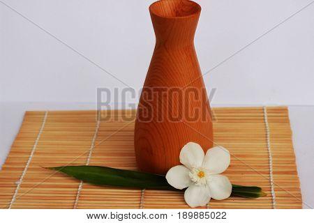 SAKE liqueur in a brown wooden bottle on a light brown background.