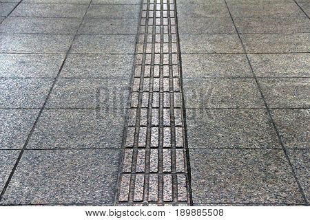 Grey braille block pavement in rectangle shape