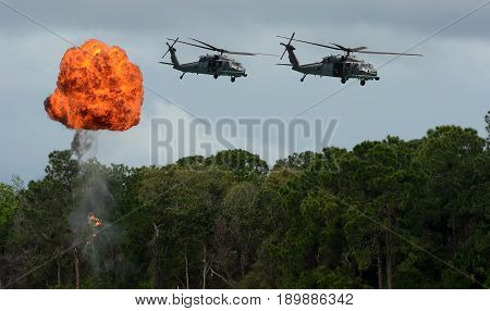 Military attack helicopters flying above explosion (simulated)