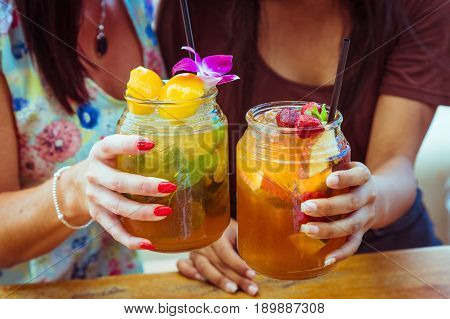 Close up of two women in colourful dresses clink glasses with refreshing strawberry apple cocktail with lime and peach mint cold coctail