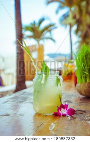 Close up of glass with tropical refreshing lemongrass coctail with mint, lime and flower decoration on palm beach background.