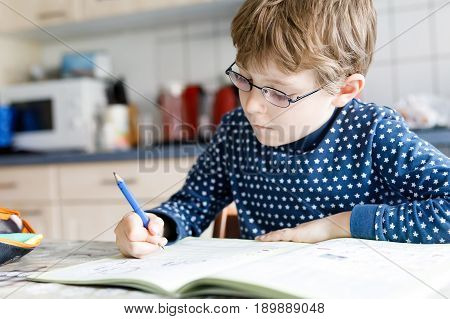 Cute little kid boy with glasses at home making homework, writing letters with colorful pens. Little child doing excercise, indoors. Elementary school and education, imagine fantasy concept.