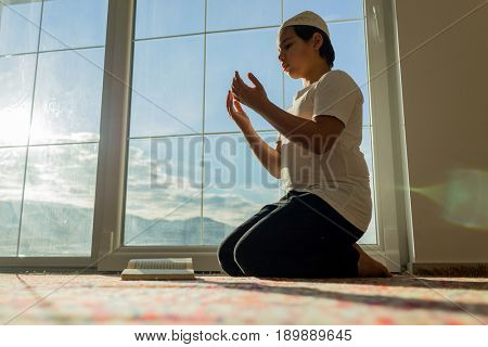 Muslim boy praying for god with his hands up