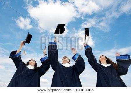 drei Studenten warf sich Hüte über blauer Himmel