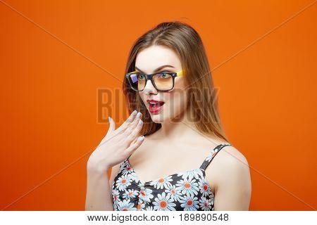 Shoked Beautiful Female Model In Eyeglasses On Orange Background. Amazing Brunette With Sensual Lips