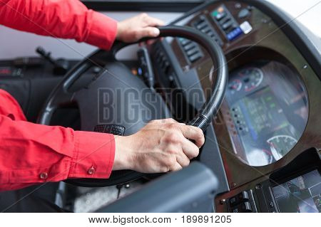 Hand close up of bus driver, driving passenger bus