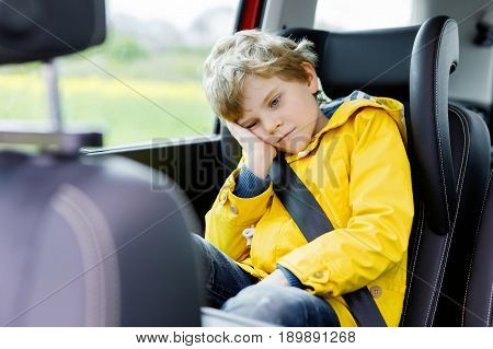 Tired preschool kid boy sitting in car during traffic jam. Sad little school child in safety car seat with belt enjoying trip and jorney. Safe travel with kids and traffic laws concept.