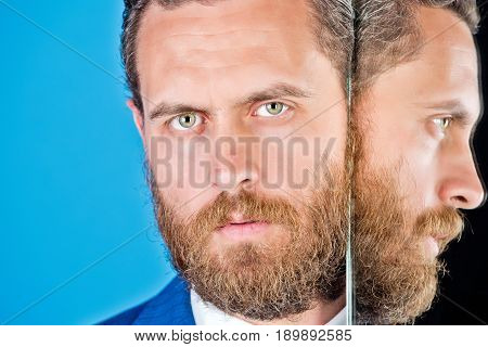 man with beard and self reflection in mirror on blue background copy space