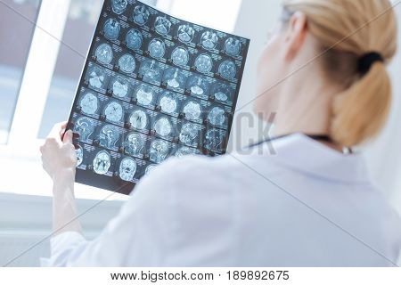 Providing radiograph before operation. Proficient experienced female neurosurgeon working at the x ray laboratory while examining brain radiograph and analyzing patient health
