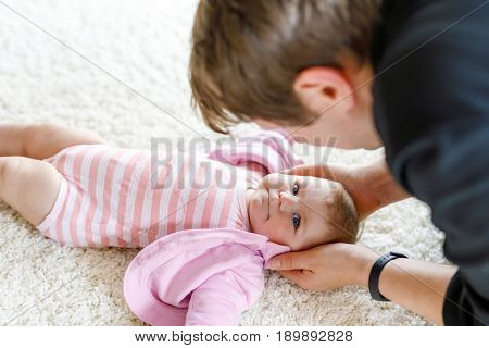 Happy proud young father having fun with newborn baby daughter, family portrait together. Dad with baby girl, love. New born child looking on dad. Bonding, family, new life