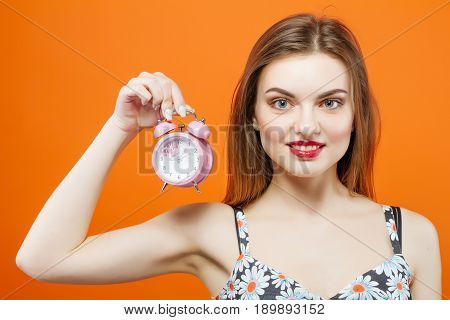 Portrait of Smiling Young Brunette with Pink Clock in Hand on Orange Background in Studio. Time Concept.