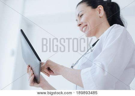 Mastering new skills . Positive lively skillful therapist enjoying working hours at the clinic while smiling and using tablet