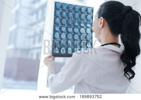 Detecting tumor in organism. Female charming smart oncologist working at the clinic while examining brain roentgen image and expressing positivity