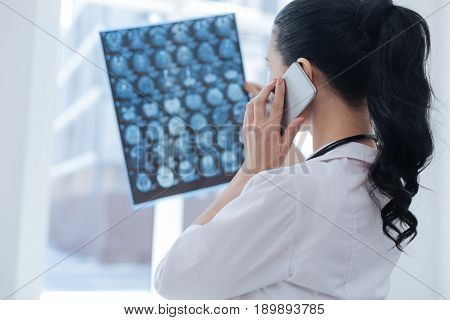 Monitoring health changes. Professional involved female oncologist working at the roentgen cabinet while examining brain scan image and using smartphone