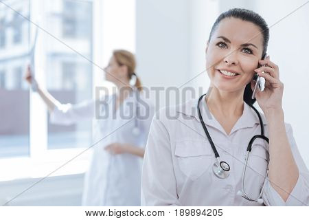 Discussing professional issues. Smiling cheerful proficient radiograph working at the clinic and enjoying conversation on the smartphone while her colleague holding mrt scan results and analyzing it