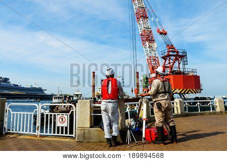 Two mature engineers with theodolite standing at construction site near the river