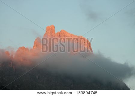 A summit of the Trentino dolomites with a cloud