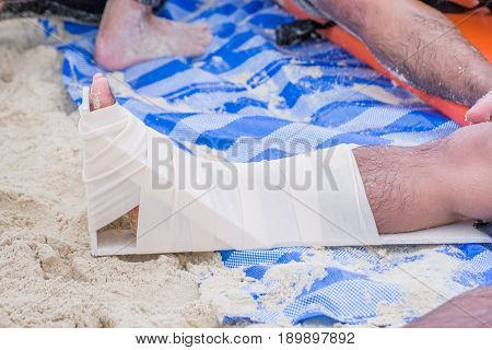 first aid by elastic bandage around right leg