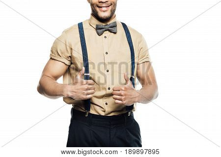 cropped view of cheerful man wearing in suspenders and bow tie showing thumbs up isolated on white