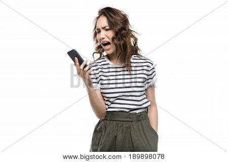 Irritated Young Woman Holding Smartphone And Screaming Isolated On White