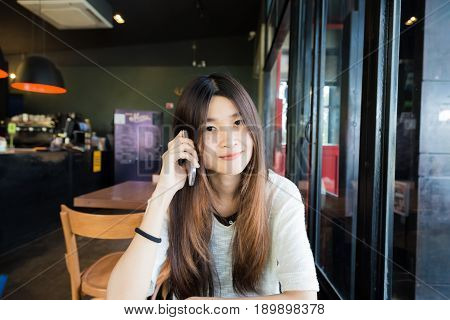 Asian Beautiful Women Talking On Smart Phone While Sitting In Cafe