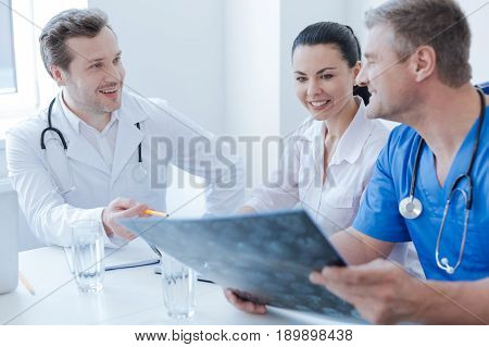 Participate in professional discussion. Friendly skillful proficient neurologists working at the clinic and examining x ray photo while enjoying conversation and taking notes