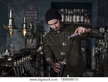 Attractive bartender is making a cocktail in a bar
