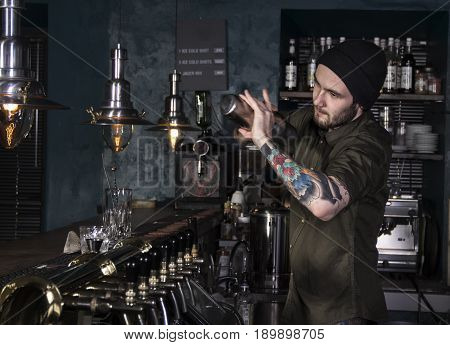 stylish bartender is mixing a fancy cocktail in  a bar