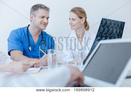 Sharing interesting medical facts. Delighted easygoing qualified doctors enjoying working hours and having conversation while other colleague using laptop in the background