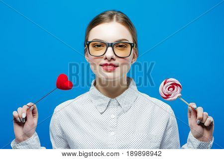 Portrait of Cute Attractive Girl with Ponytail and Eyeglasses Holding Heart and Big Lollipop in Hands in Studio on Blue Background. Pretty Brunette with Red Lips in Shirt.