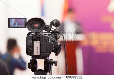 Filming an media event with a video camera. Press conference.