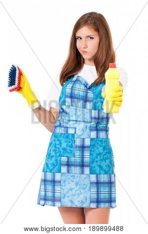 Tired young woman holding bottle of chemistry for cleaning house. Cleaning concept. Beautiful girl with cleaning tools and products on white background. Housekeeper isolated portrait.