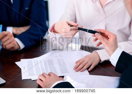 Business women giving a pen to business man for contract signing.