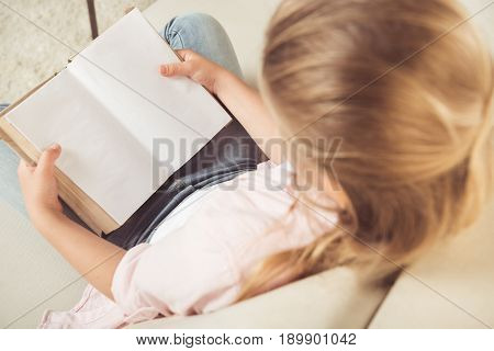 Overhead View Of Schoolgirl Holding Empty Book While Sitting On Sofa At Home