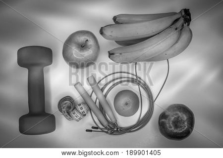 healthy eating concept. Dumbbell, rope, bananas, orange, measuring tape waist, oranges, red apple, green apple, on a white table. healthy lifestyle. sport. Fitness diet. Black and white concept.