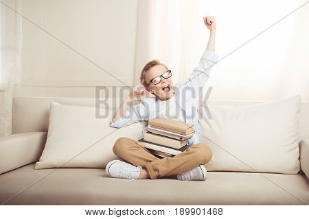 Adorable Little Boy In Eyeglasses Sitting On Sofa With Books Stretching And Yawning