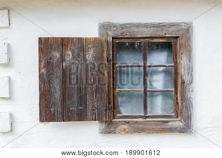 An old antique window in a vintage peasant white house in Ukraine. Ancient peasant Ukrainian house in the spring with a thatched roof in the old village of national architecture Ukraine. National Museum Pirogovo in the outdoors near Kiev.