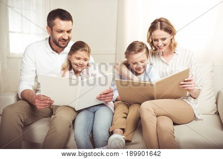 Happy Family With Two Adorable Children Sitting Together And Reading Books At Home