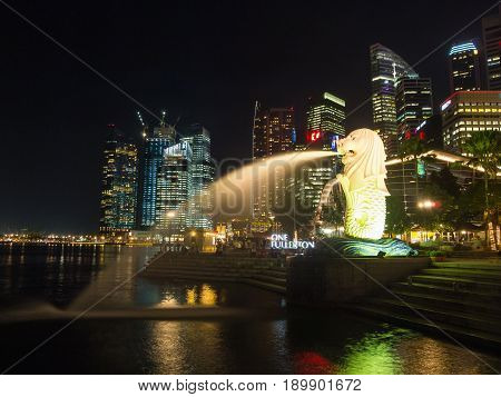 Singapore Singapore - Oct 10 2011: Merlion statue fountain and city skyline at night. This place is famous tourist attraction in singapore