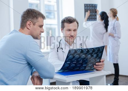 Explaining all details of treatment. Mature experienced confident therapist enjoying appointment with patient and analyzing mrt scan while nurses enjoying discussing in the background