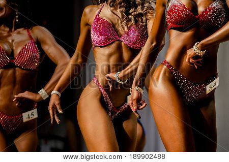 three young girls in swimsuits competition fitness bikini