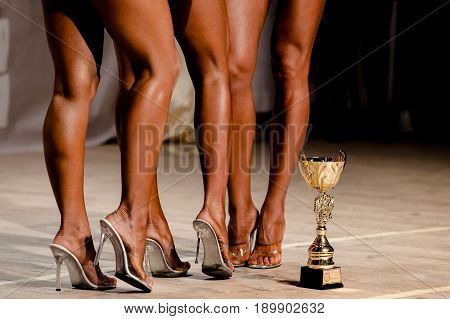 slender legs of women athletes with Cup winner in competition fitnes bikini