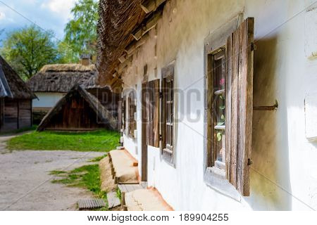 Ancient peasant Ukrainian house in the spring with a thatched roof in the old village of national architecture Ukraine. Ancient peasant Ukrainian house in the spring with a thatched roof in the old village of national architecture Ukraine. National Museum