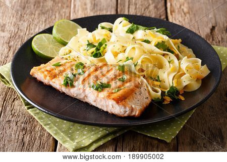 Pasta Fettuccine With Cheese And Butter And Grilled Salmon With Herbs Close-up. Horizontal