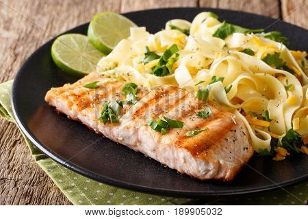 Salmon Grilled With Fettuccine Pasta And Cheese Close-up. Horizontal
