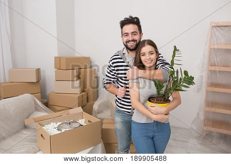 Relocation of young happy family to newl apartment. Happy man and woman standing in new flat ready to unpack boxes.