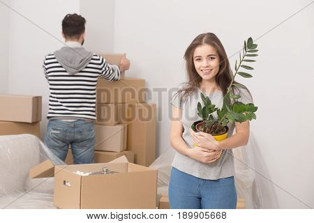 Young couple relocating to new apartment and unpacking boxes. Front view of young woman holding plant and man standing behind unpacking boxes.
