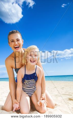 Happy Young Mother And Daughter On Seacoast Having Fun Time