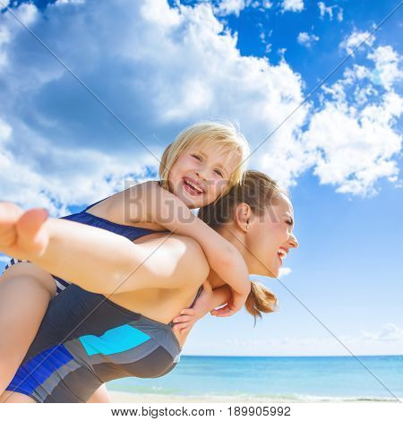 Cheerful Healthy Mother And Child On Seacoast Having Fun Time